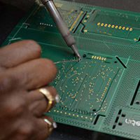Employee testing PCB circuits